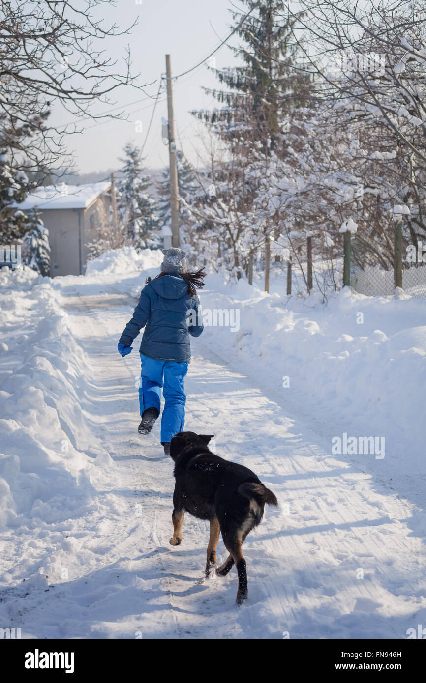 Dog chasing woman down the street in snow - Stock Image