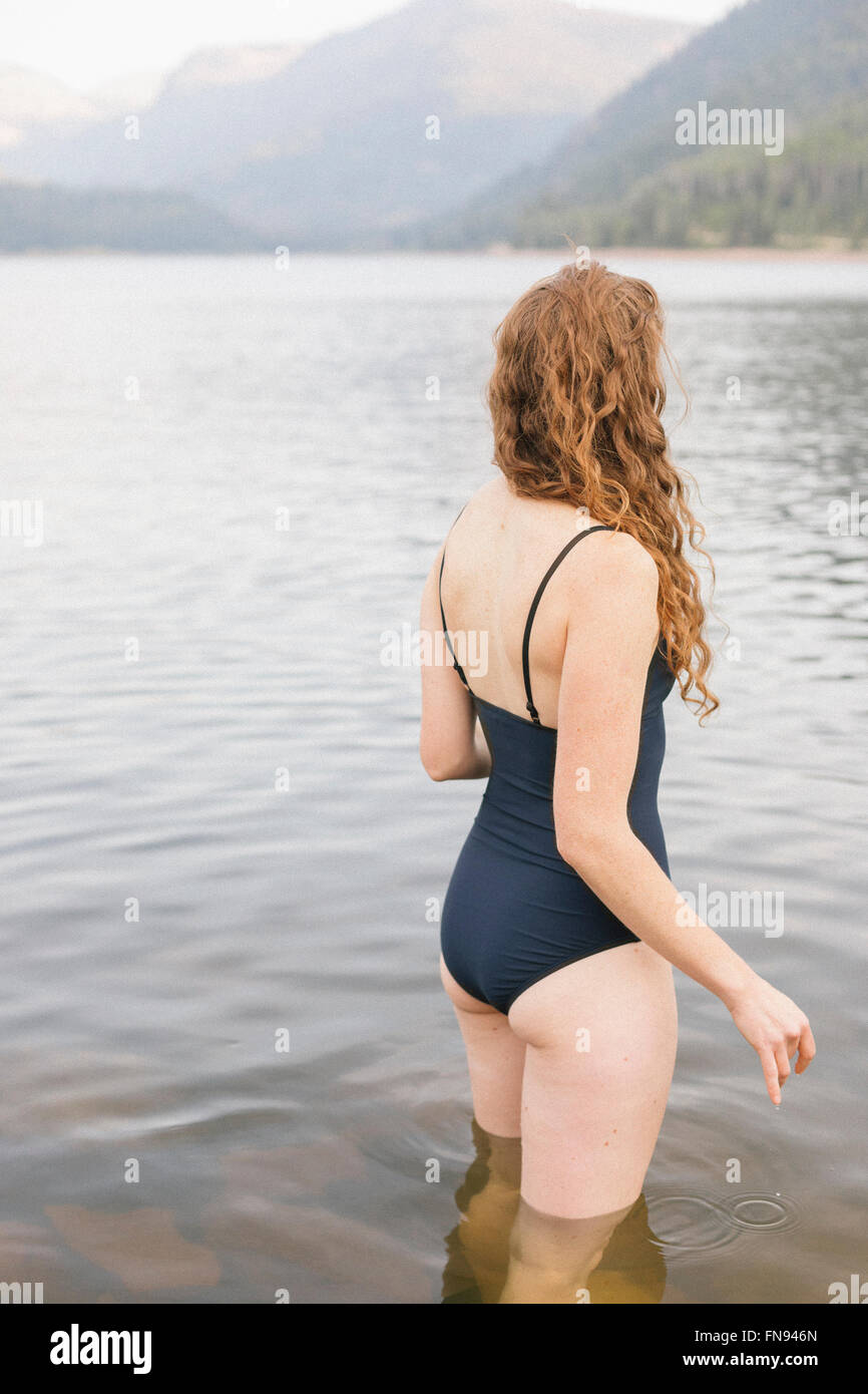 A woman in a black swimsuit wading into a calm lake in the mountains. - Stock Image