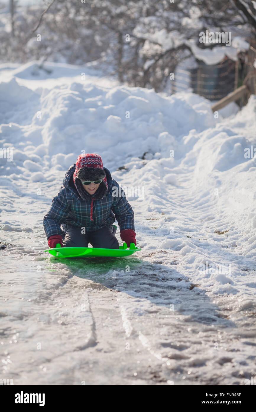Boy kneeling on a sledge - Stock Image