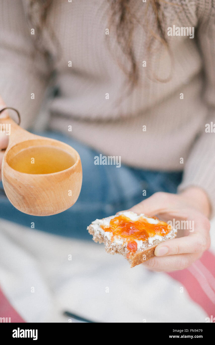A woman holding a cup of tea and a slice of bread and jam. - Stock Image