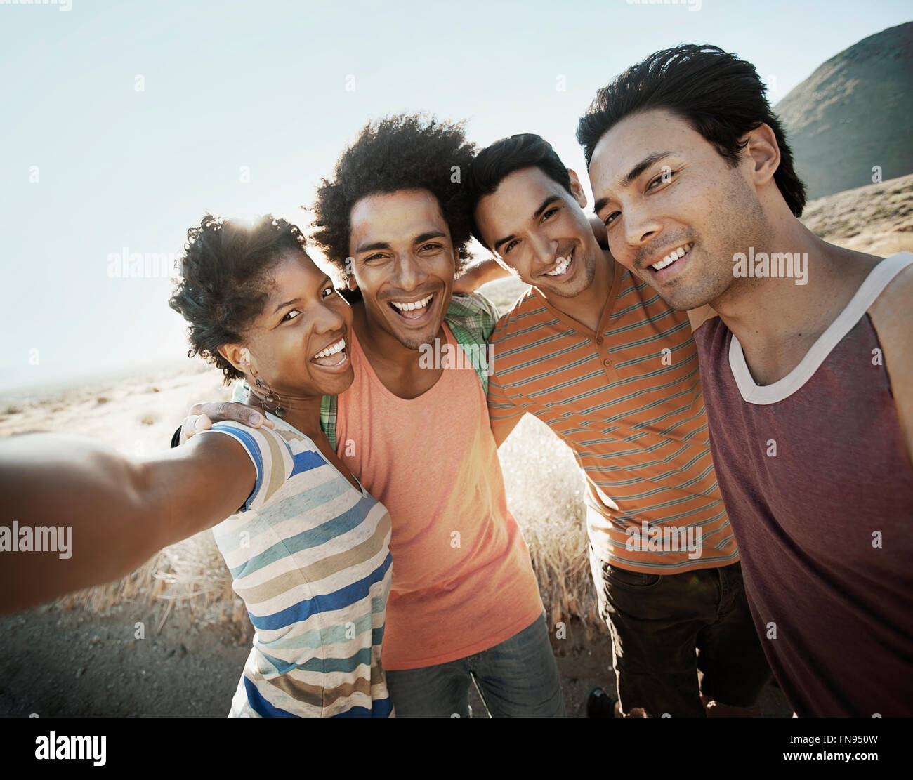 A group of friends, men and women, heads together posing for a selfy in the heat of the day. - Stock Image