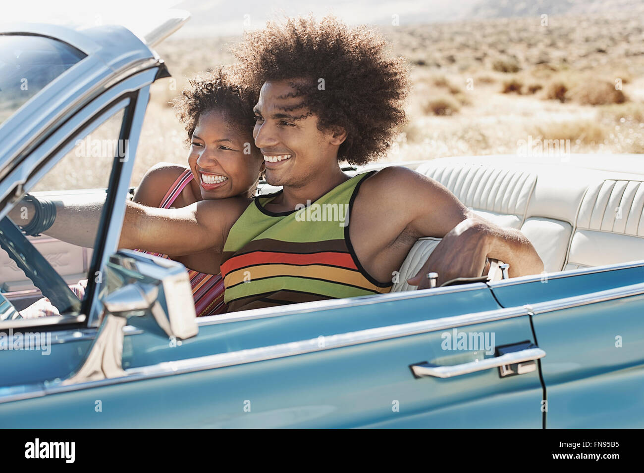 A young couple, man and woman in a pale blue convertible on the open road - Stock Image