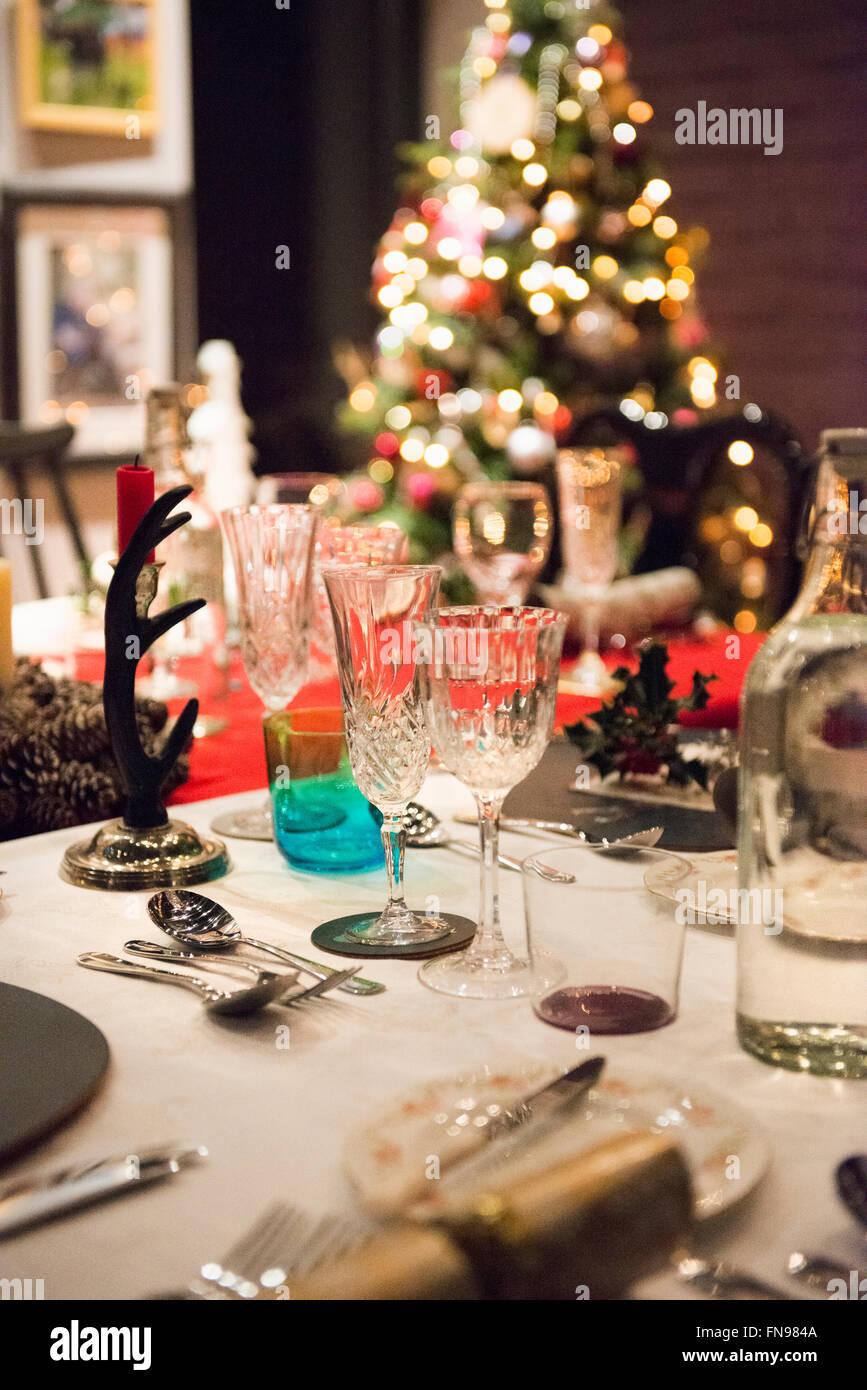 A table laid for a Christmas meal, with silver and crystal glasses and a Christmas tree in the background. - Stock Image