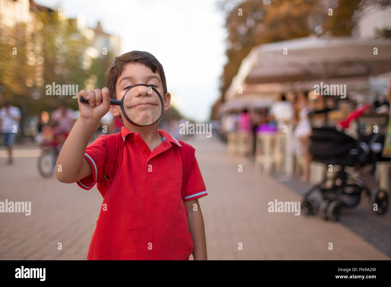 Young boy smiling through magnifying glass, sofia, bulgaria - Stock Image