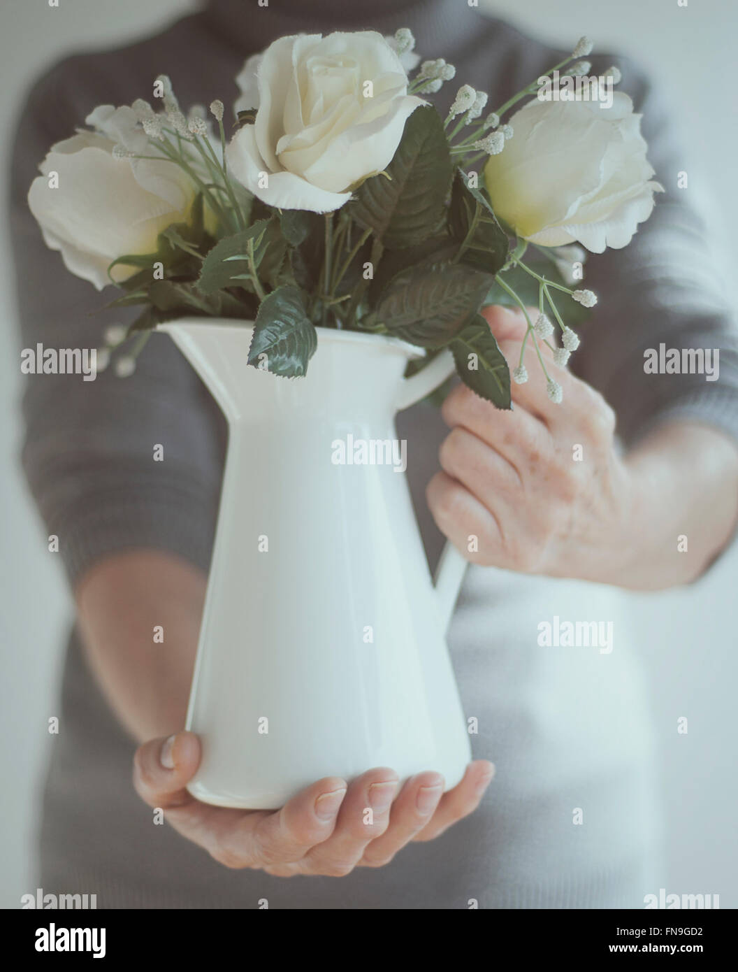 Senior man holding a jug of flowers Stock Photo
