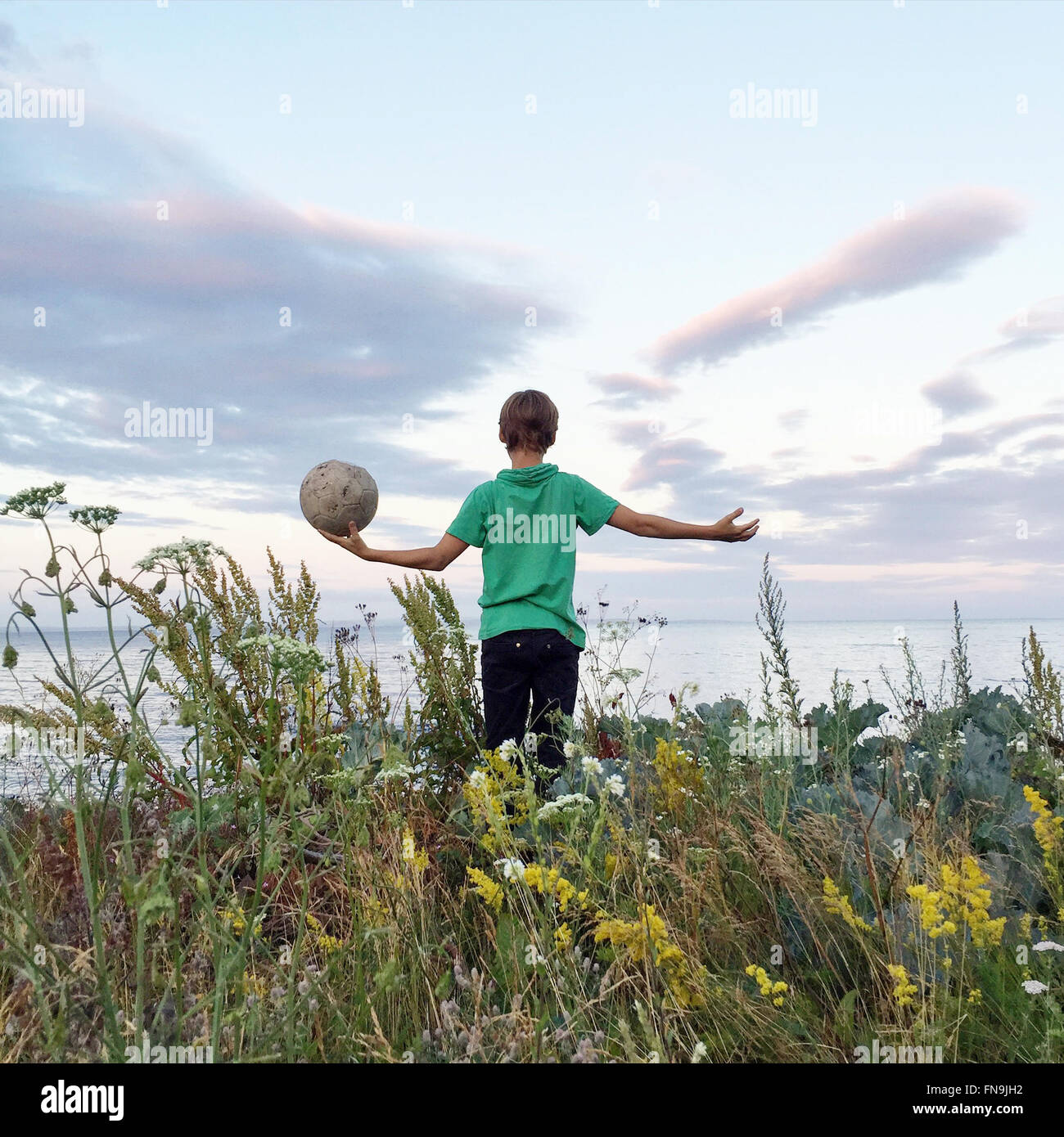 Boy standing in a field holding a football, Ringshaug, Tonsberg, Norway - Stock Image