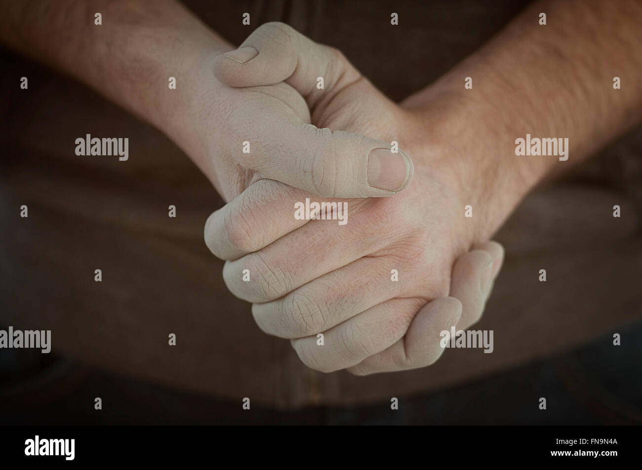 Close up of man's hands clasped - Stock Image