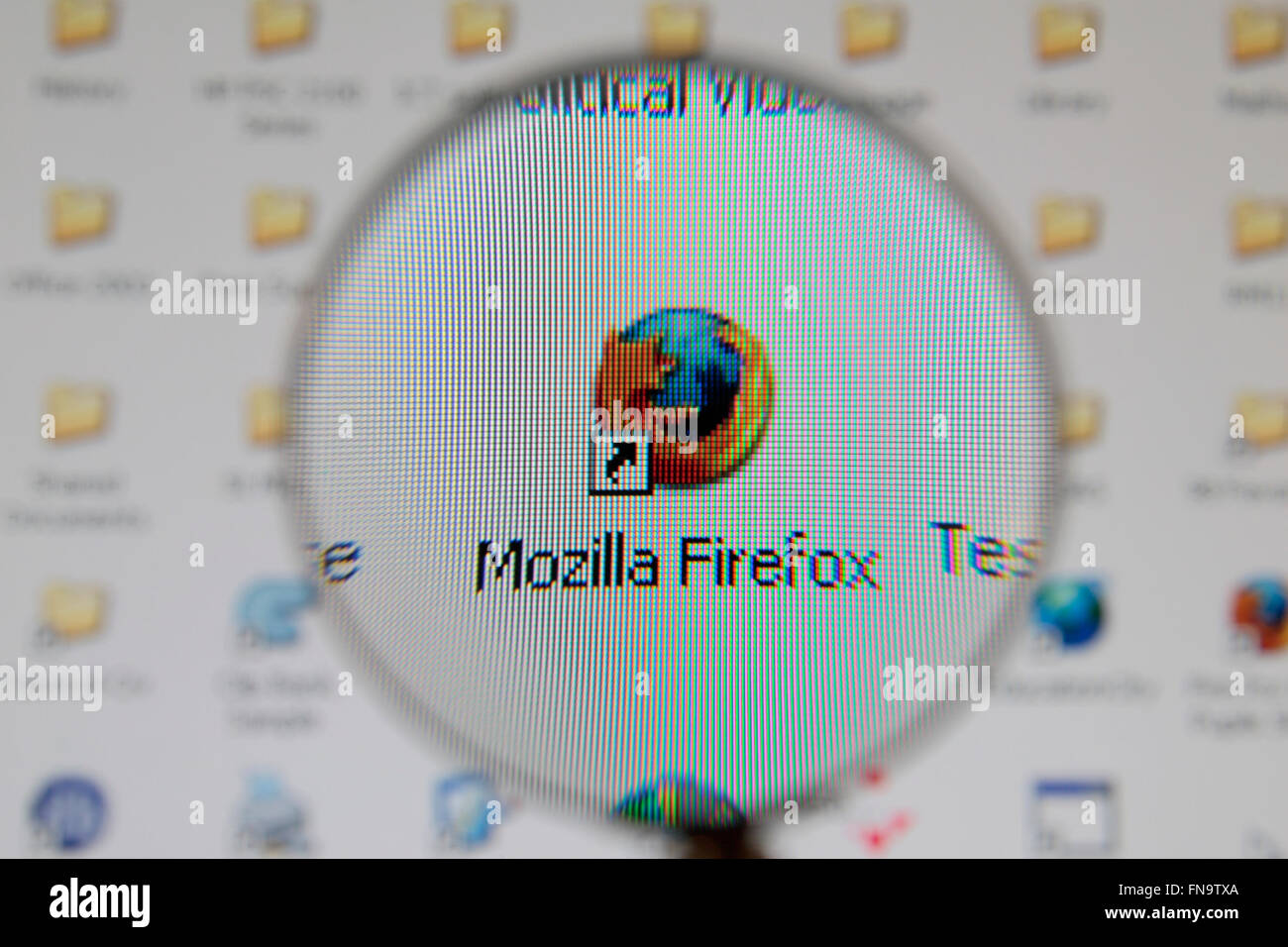 The Mozilla Firefox logo on a windows desktop computer as viewed through a magnifying glass. - Stock Image