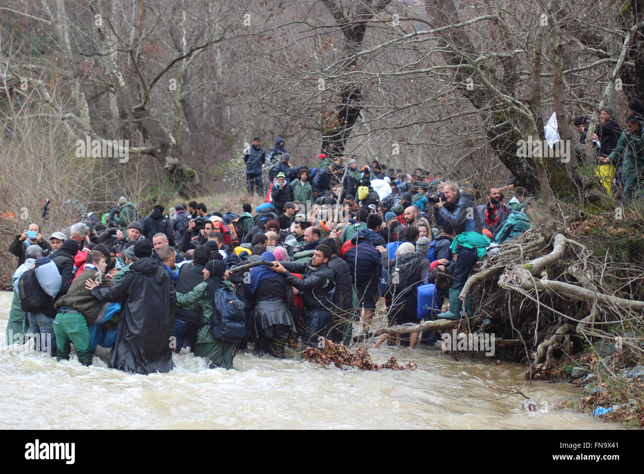 Refugees crossing a stream that became a torrent due to the rain in the past days, Chamilo, Greece, 14 March 2016. - Stock Image