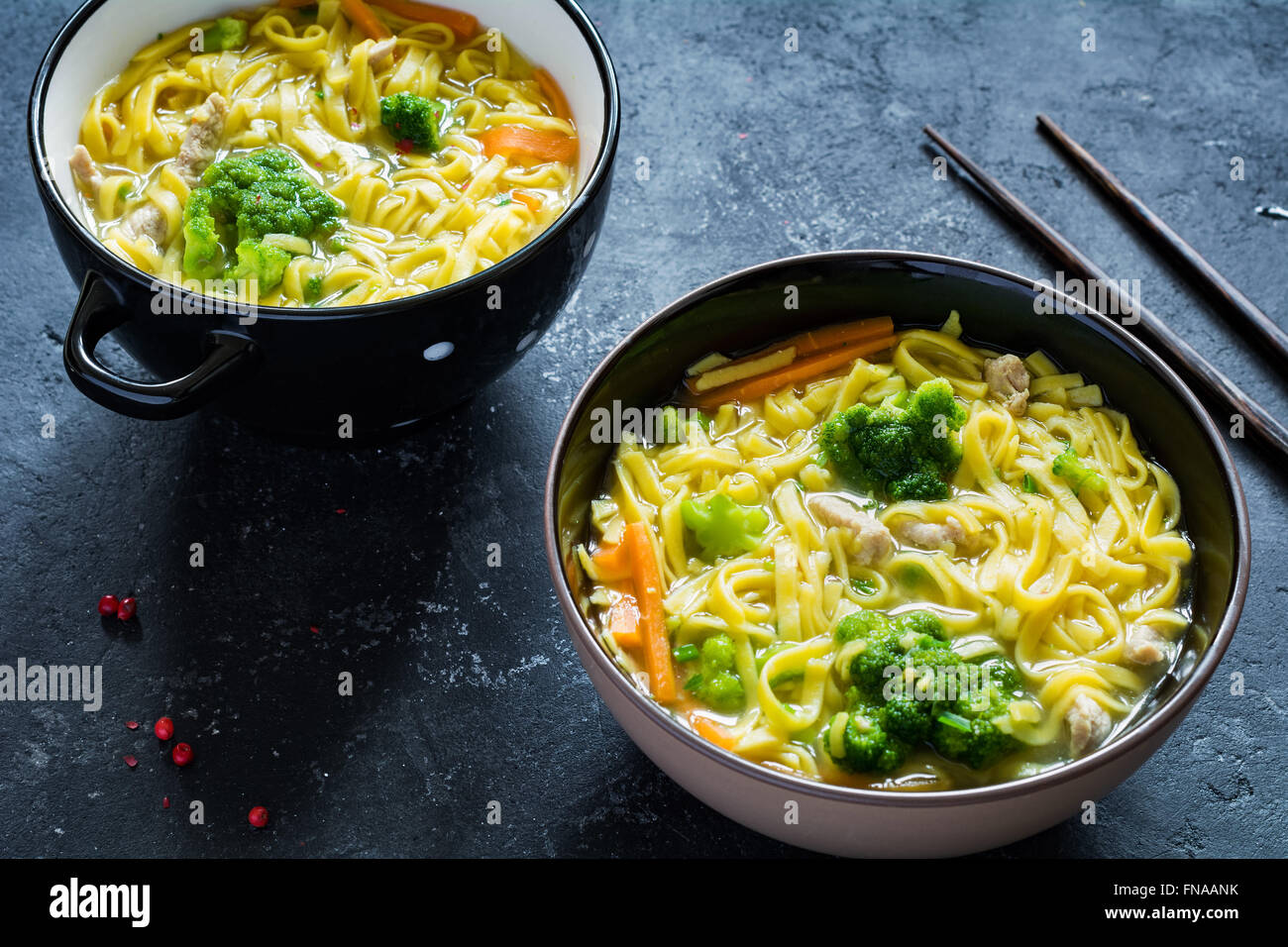 Asian egg noodle soup with vegetables and pork on dark slate background. Top view - Stock Image