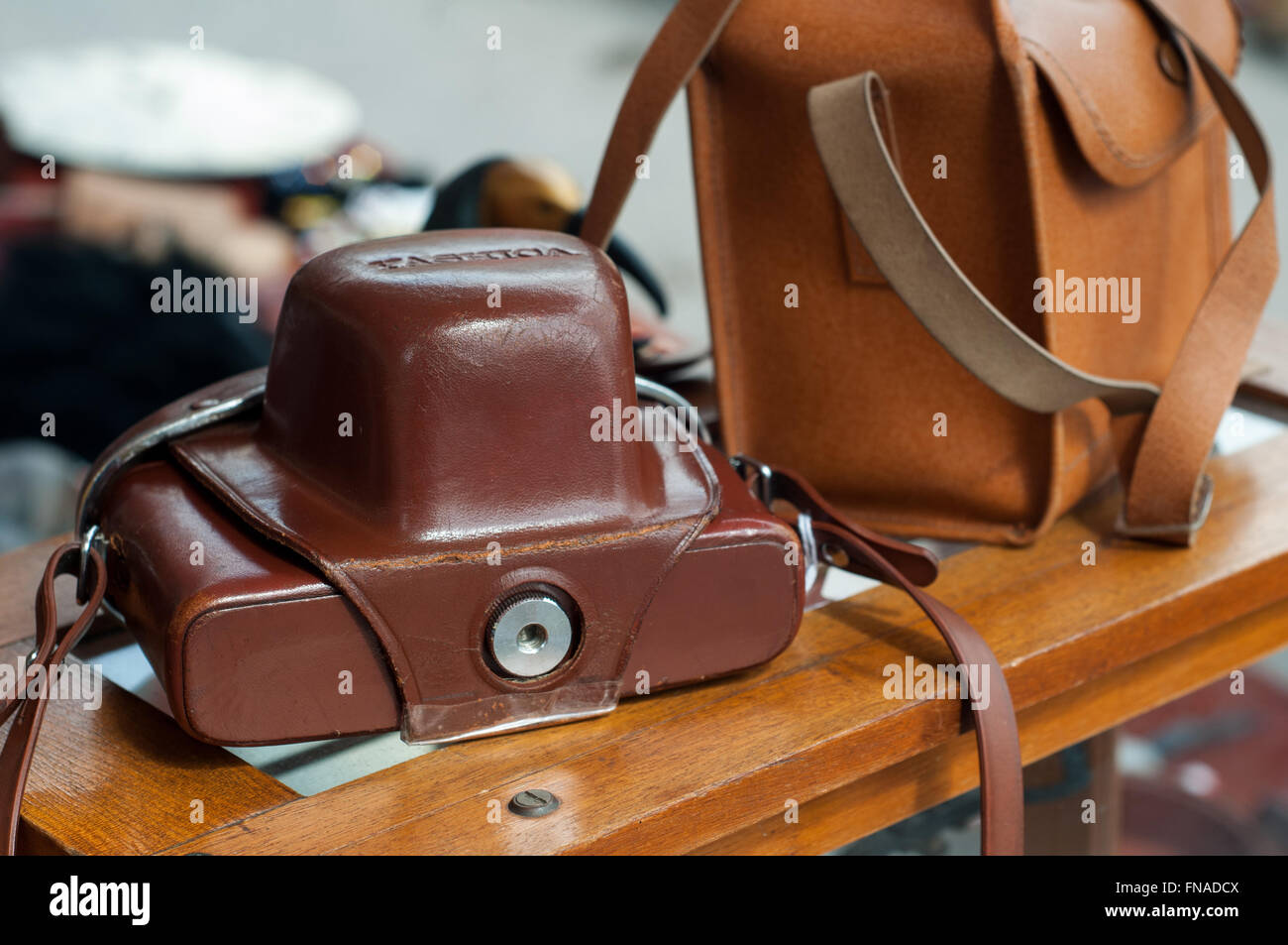 Old vintage 35mm slr camera in leather case pouch on photography market stall at carboot sale in Bath, UK. - Stock Image