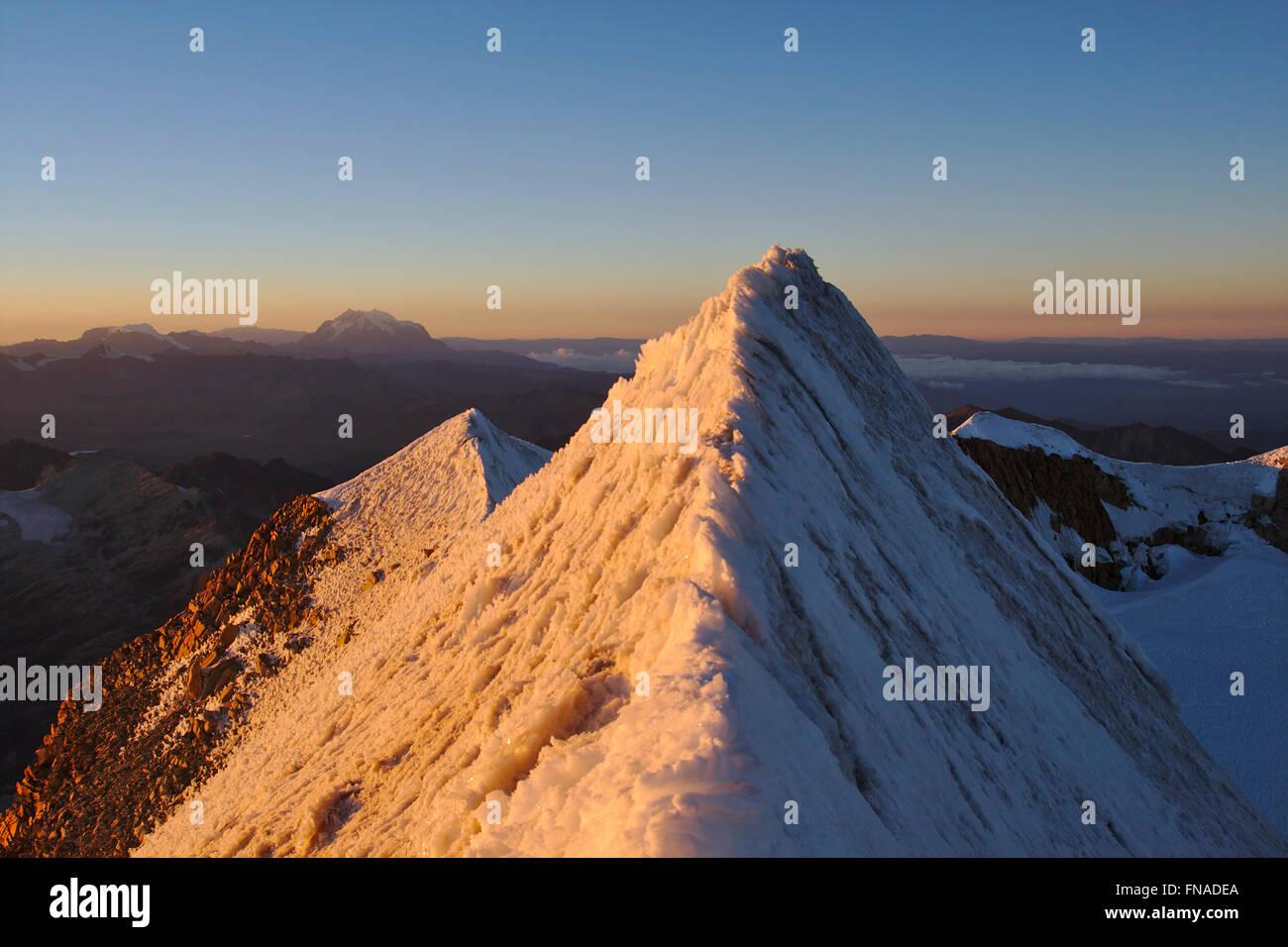 Summit ridge of Huayna Potosi in the Cordillera Real, sunrise, Illimani in the distance, Bolivia - Stock Image