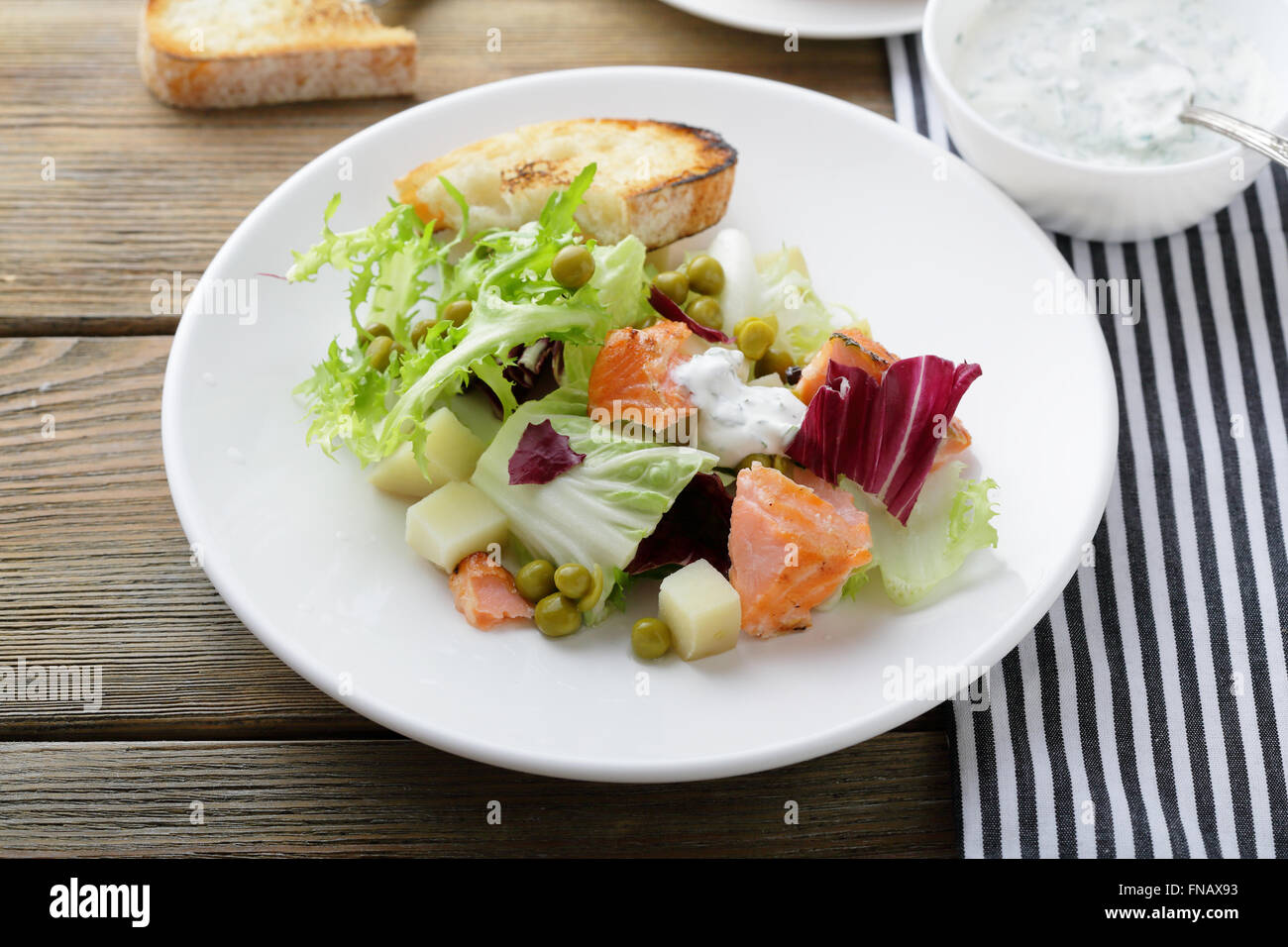salad with baked fish, food closeup - Stock Image