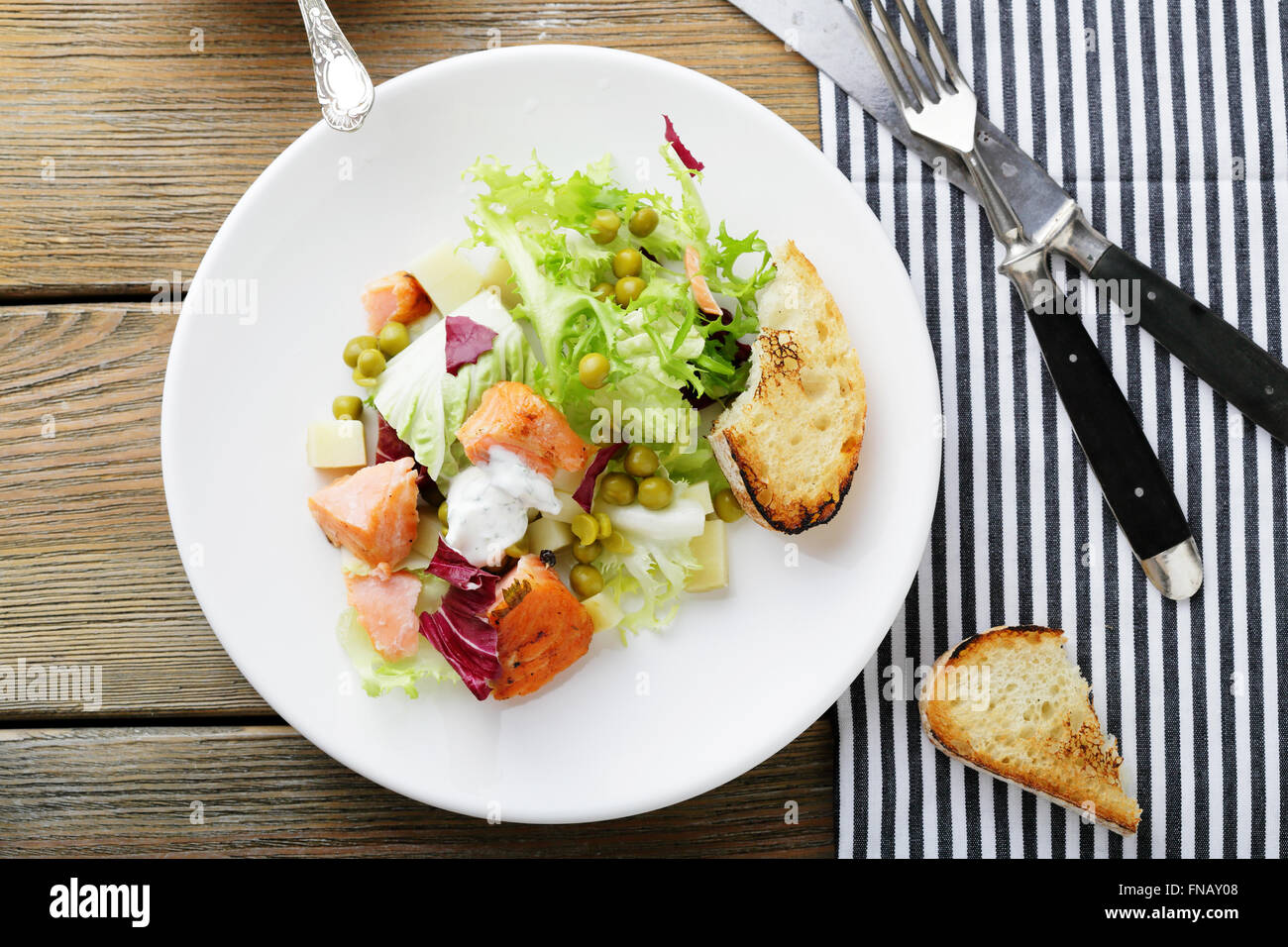 salad with slice of roasted fish, food top view - Stock Image