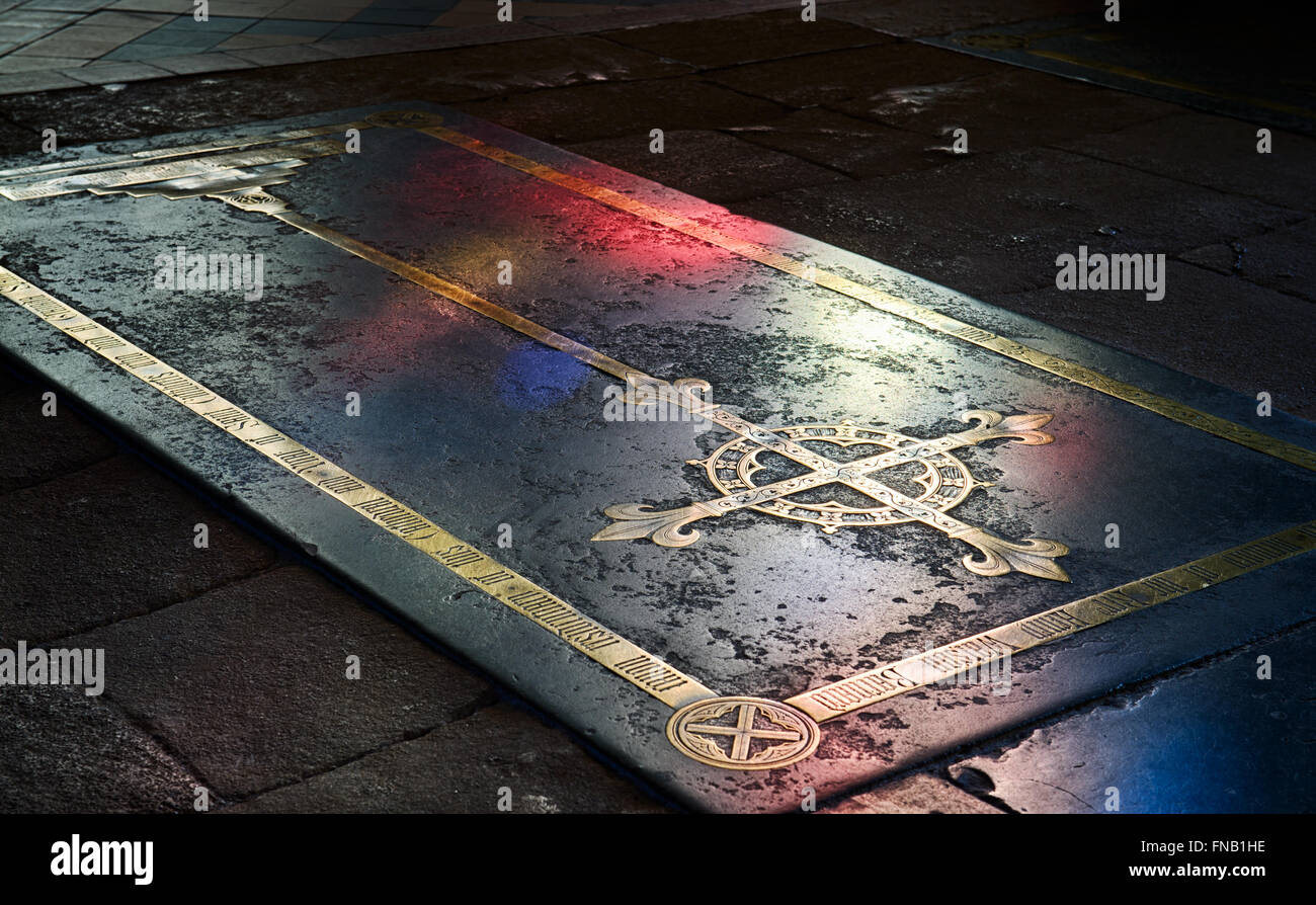 Black purbeck ledger with victorian brass inlaid cross on the floor of the retrochoir in Wells Cathedral. Somerset. - Stock Image