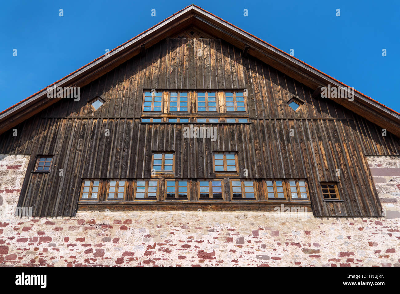 Gable of a rustic house with a dark brown wooden facade above a foundation wall made of red natural stone - Stock Image
