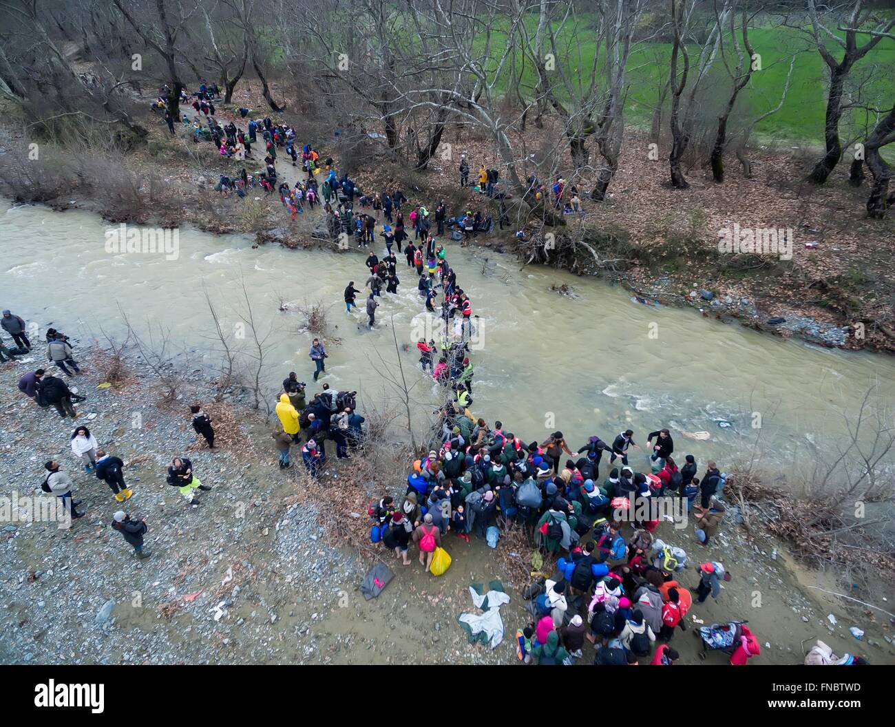 Chamilo, Greece. 14th March, 2016. Refugees try to cross a stream near the Greek village of Chamilo on March 14, Stock Photo