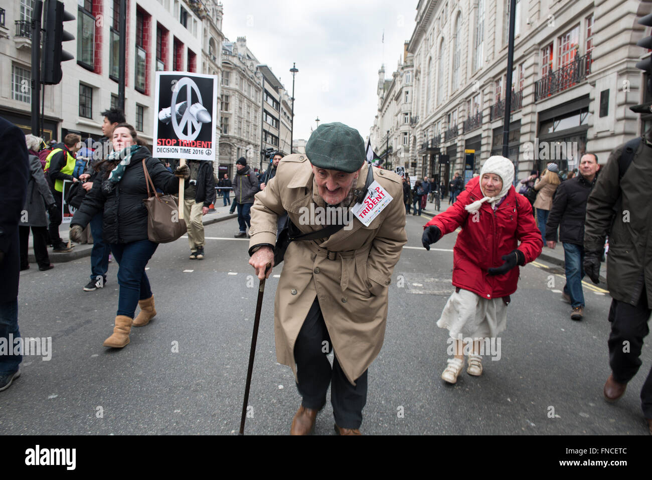 An elderly man with a stick is running near the Piccadilly Square protesting against the renewal of Trident Nuclear - Stock Image