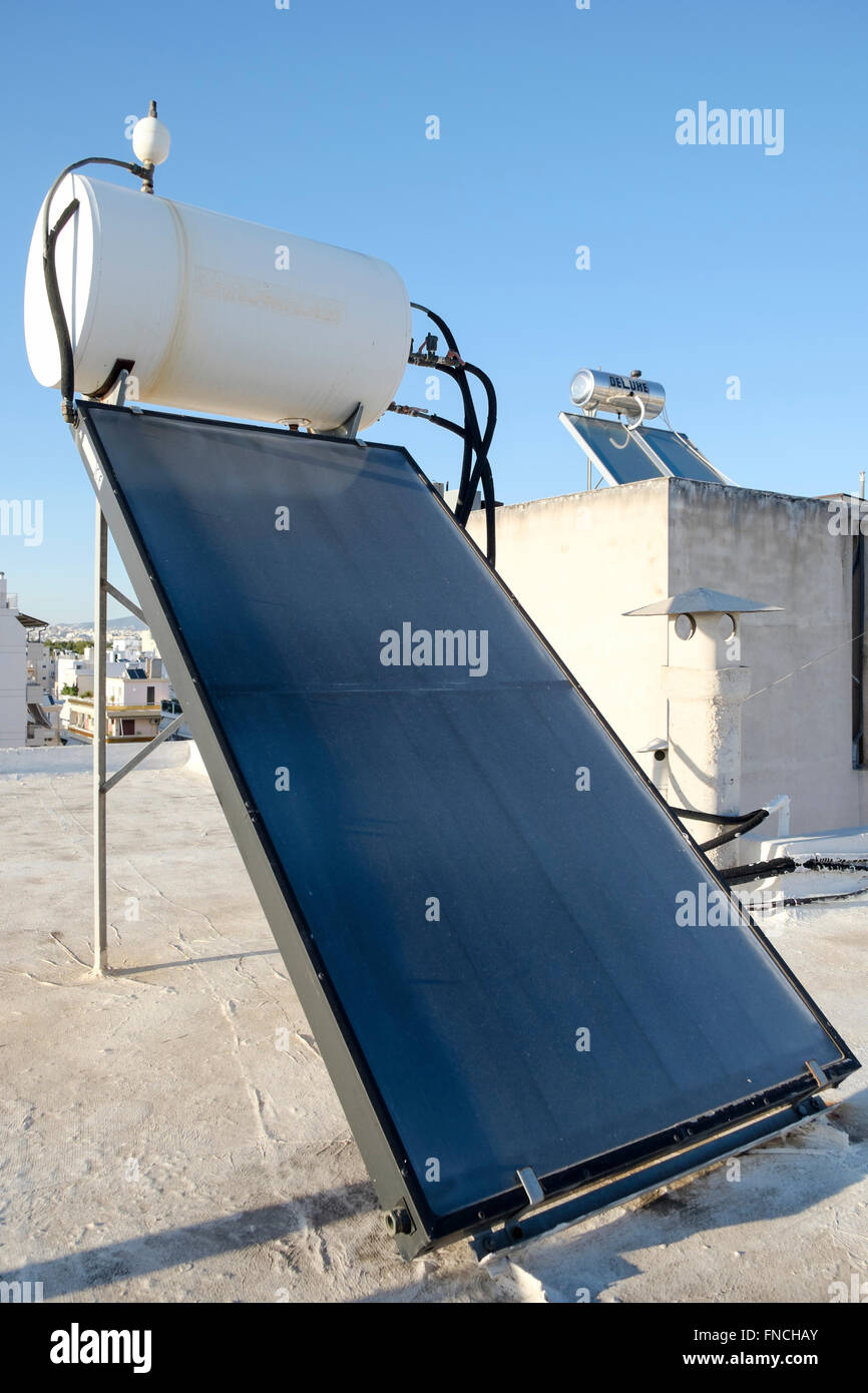 Solar hot water heaters on rooftops in Athens, Greece. - Stock Image