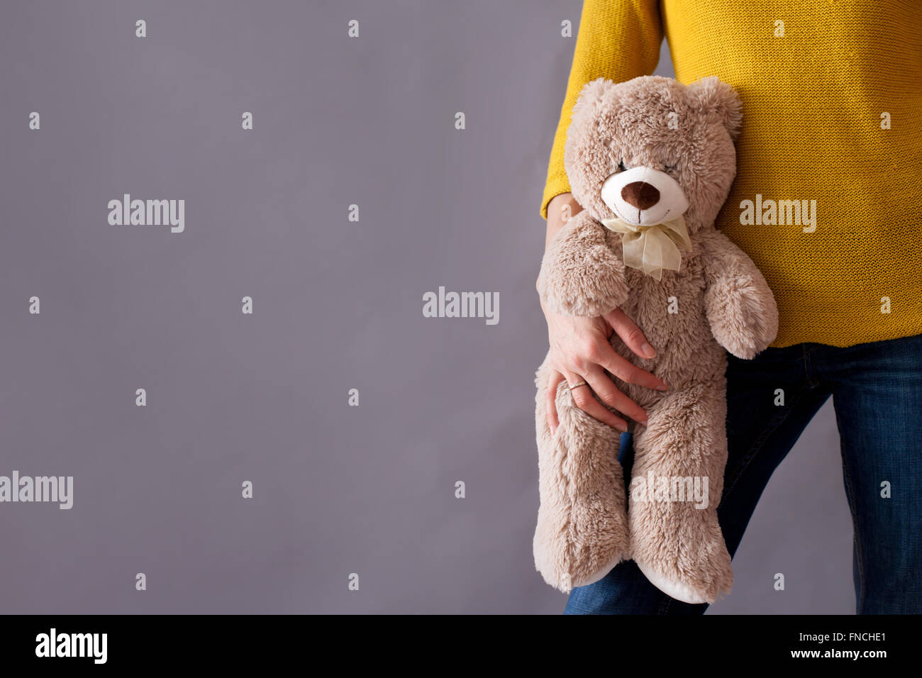 Young girl, holding sweet fluffy teddy bear, isolated image - Stock Image