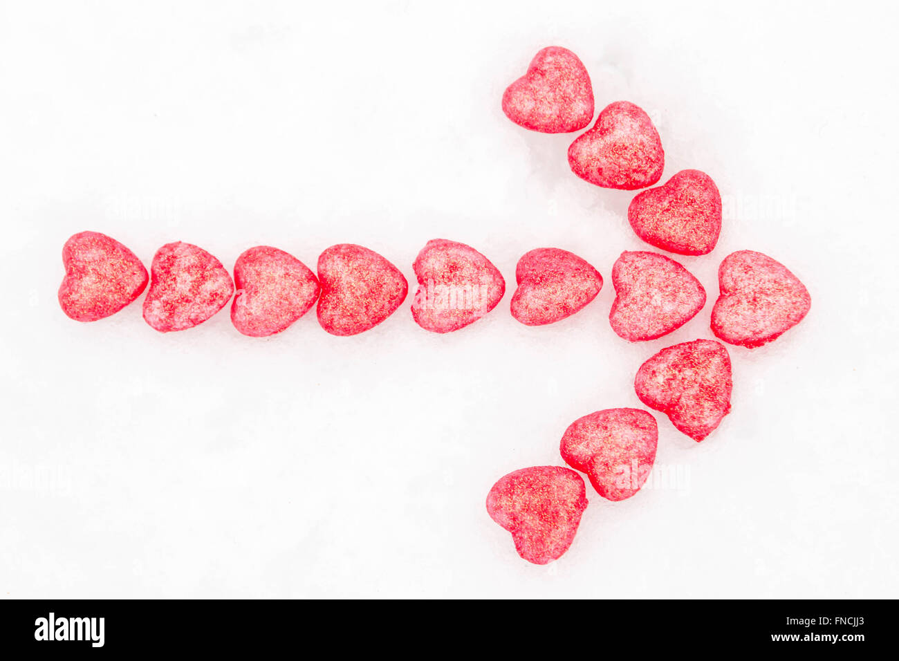 Arrow of pink hearts in the snow - Stock Image