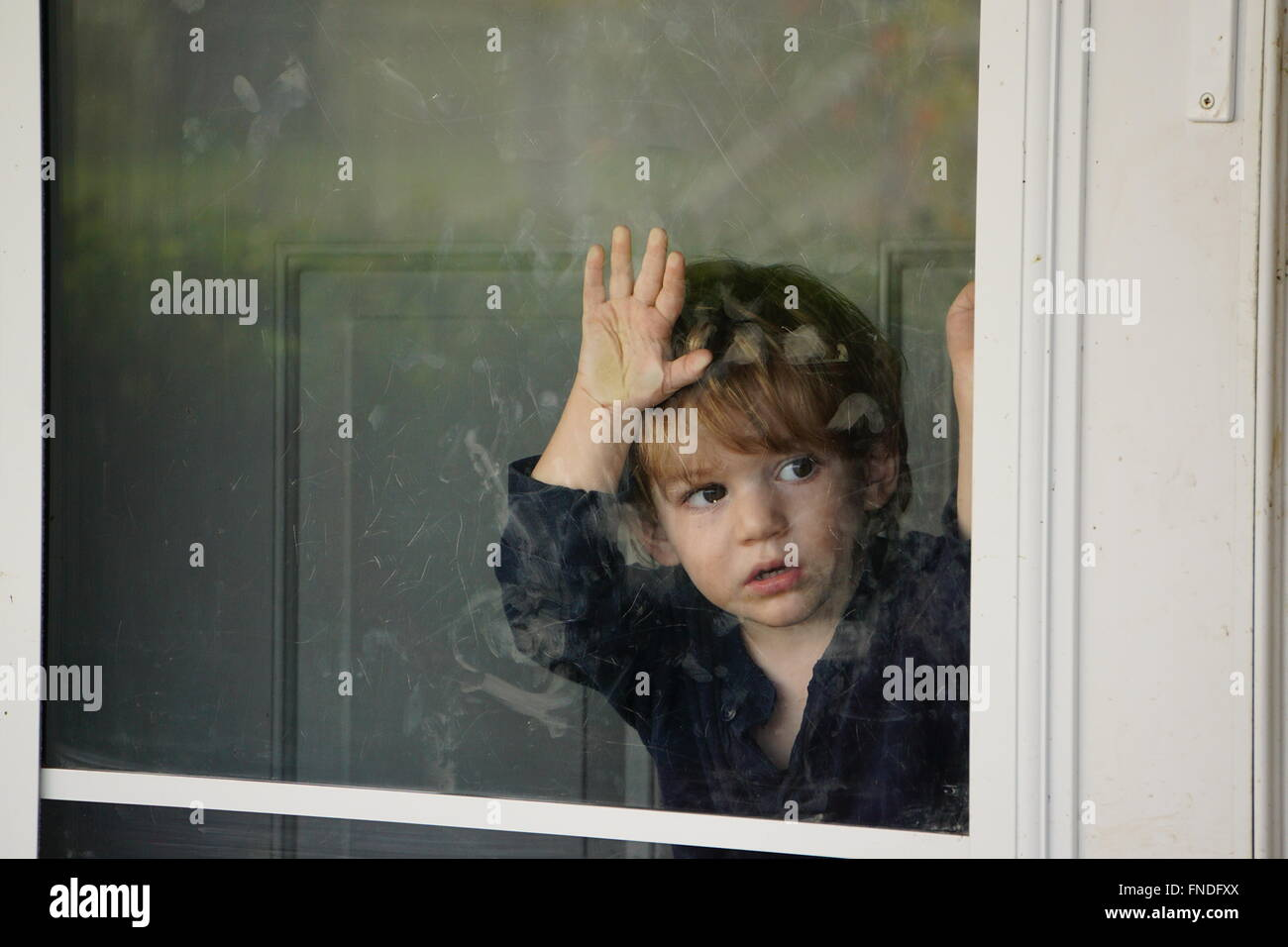Boy looking outside through a glass door - Stock Image
