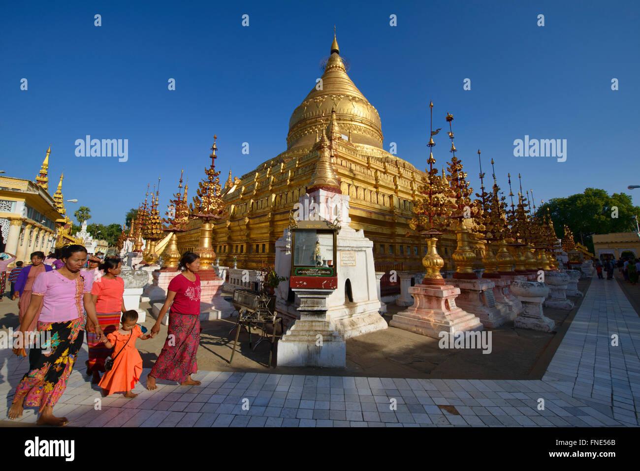Pilgrims walking at golden Shwezigon Pagoda, Bagan, Myanmar Stock Photo