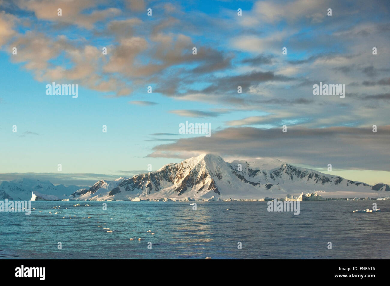 Snowy rocks in morning light, cloudy atmosphere, Antarctic Peninsula, Antarctica - Stock Image