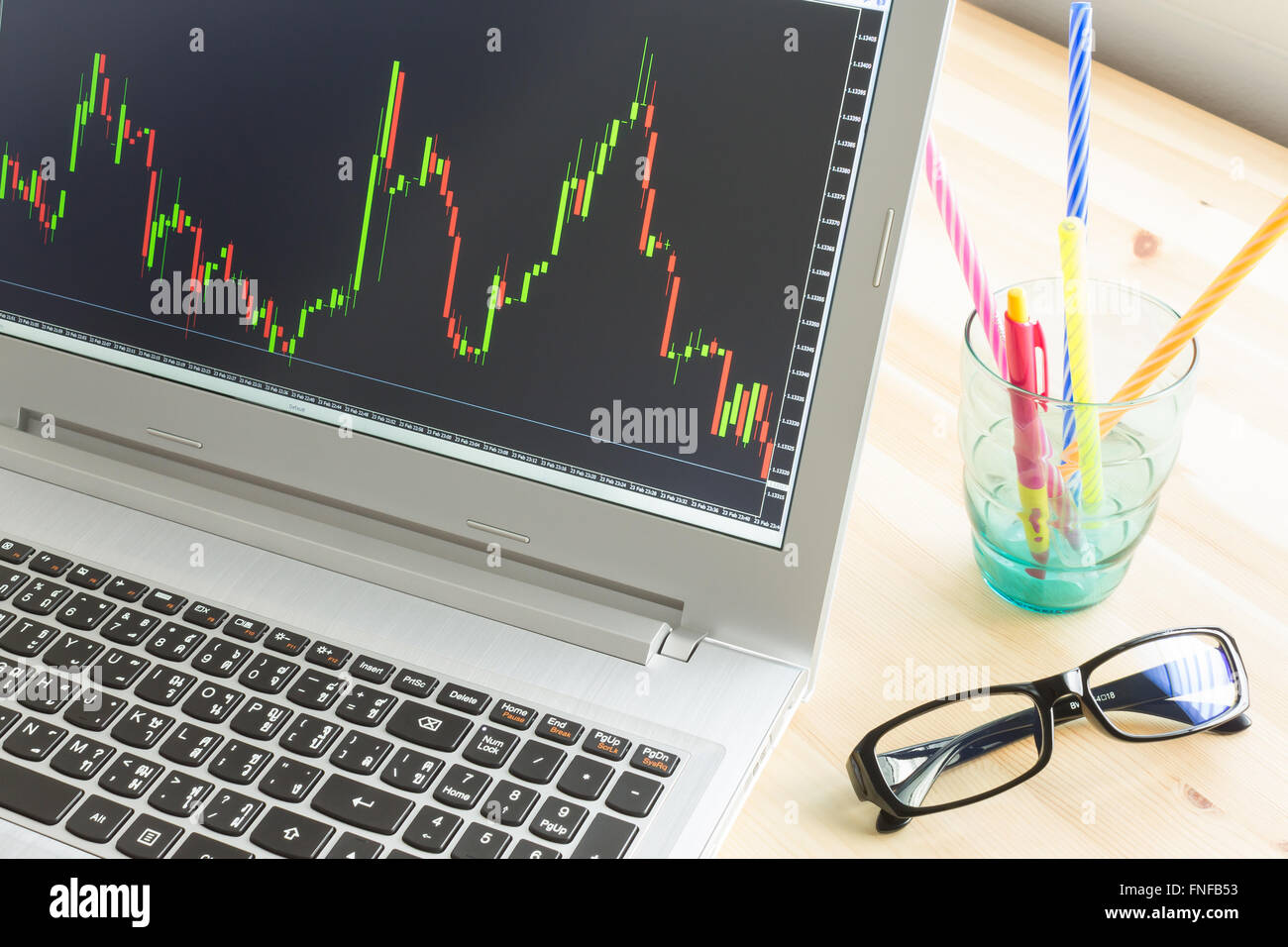 Forex graph or stock graph in laptop screen on wood table and pen and black glasses - Stock Image