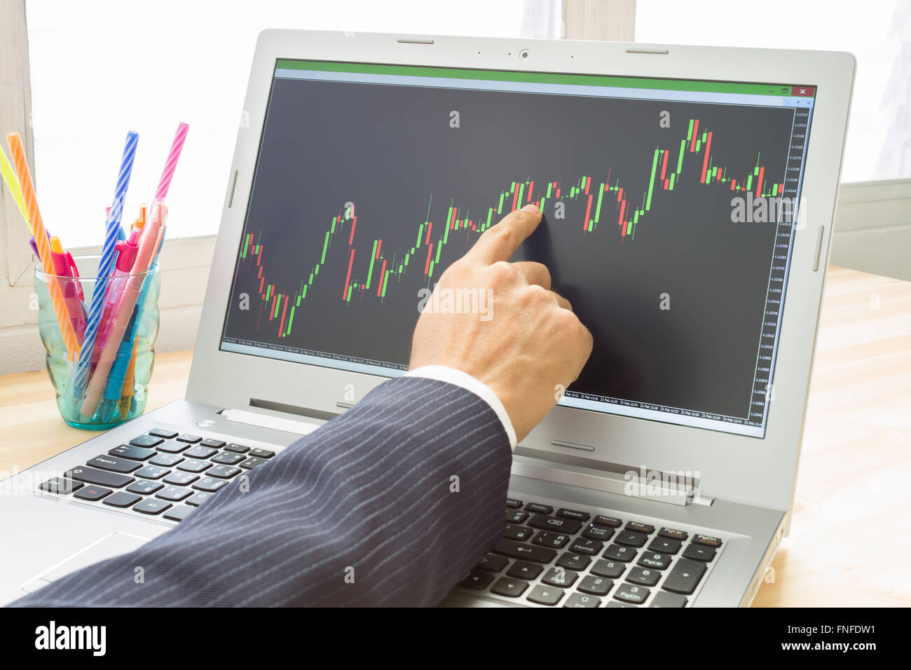 Businessman is pointing stock graph or forex graph . Technical analysis forex or stock by professional trader with - Stock Image