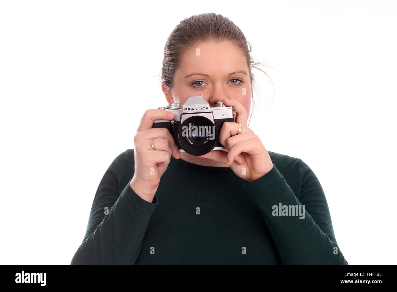 Young attractive woman holding an old East German film slr, Praktica L2. - Stock Image