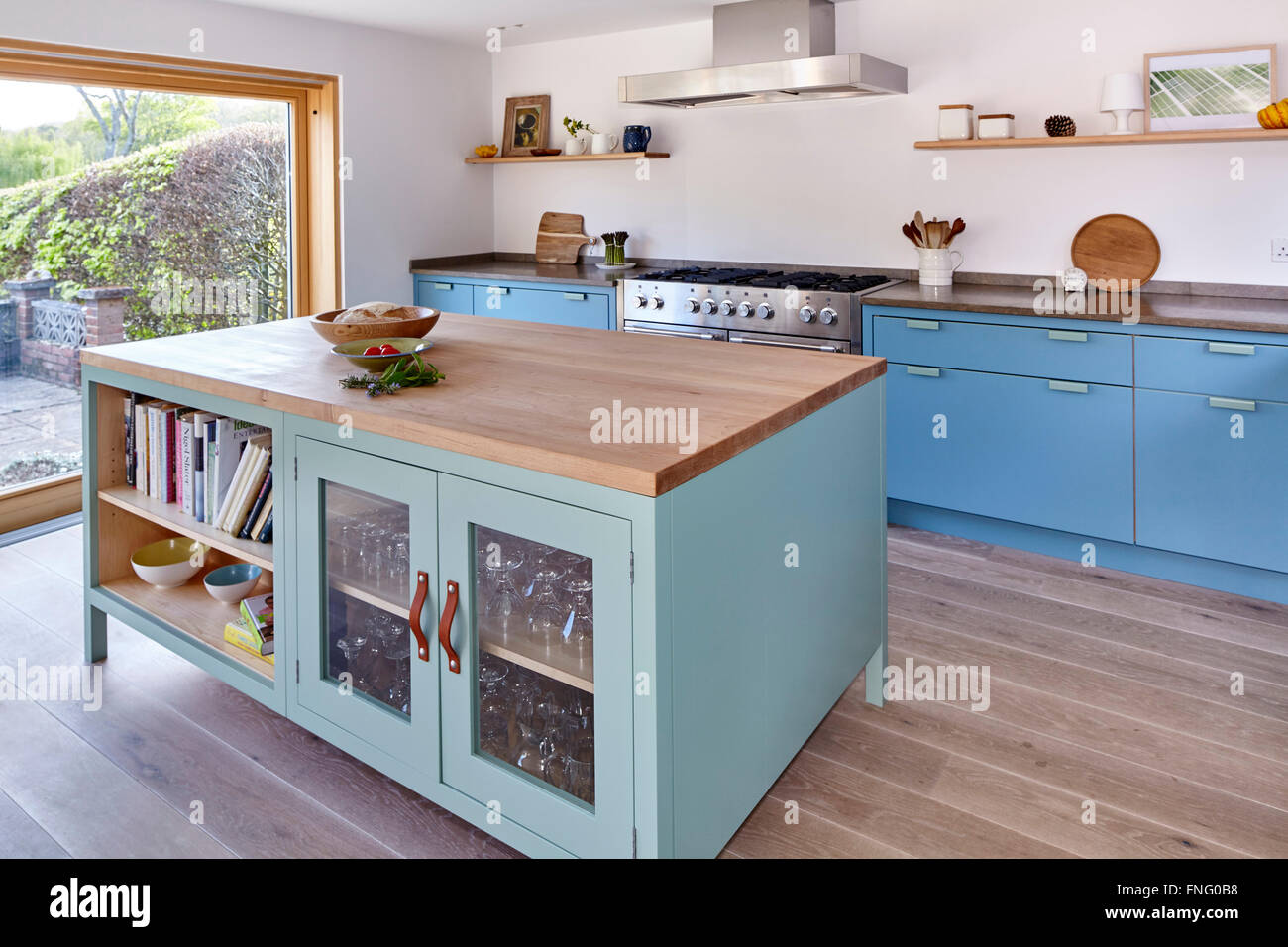 Oblique view of contemporary kitchen design with island, shelves and glass doors. Mill Race House, Hungerford, United - Stock Image