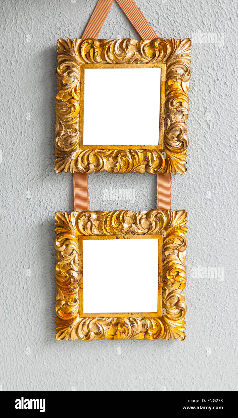 Image of ornate gilded mockup frames hanging on a wall. - Stock Image