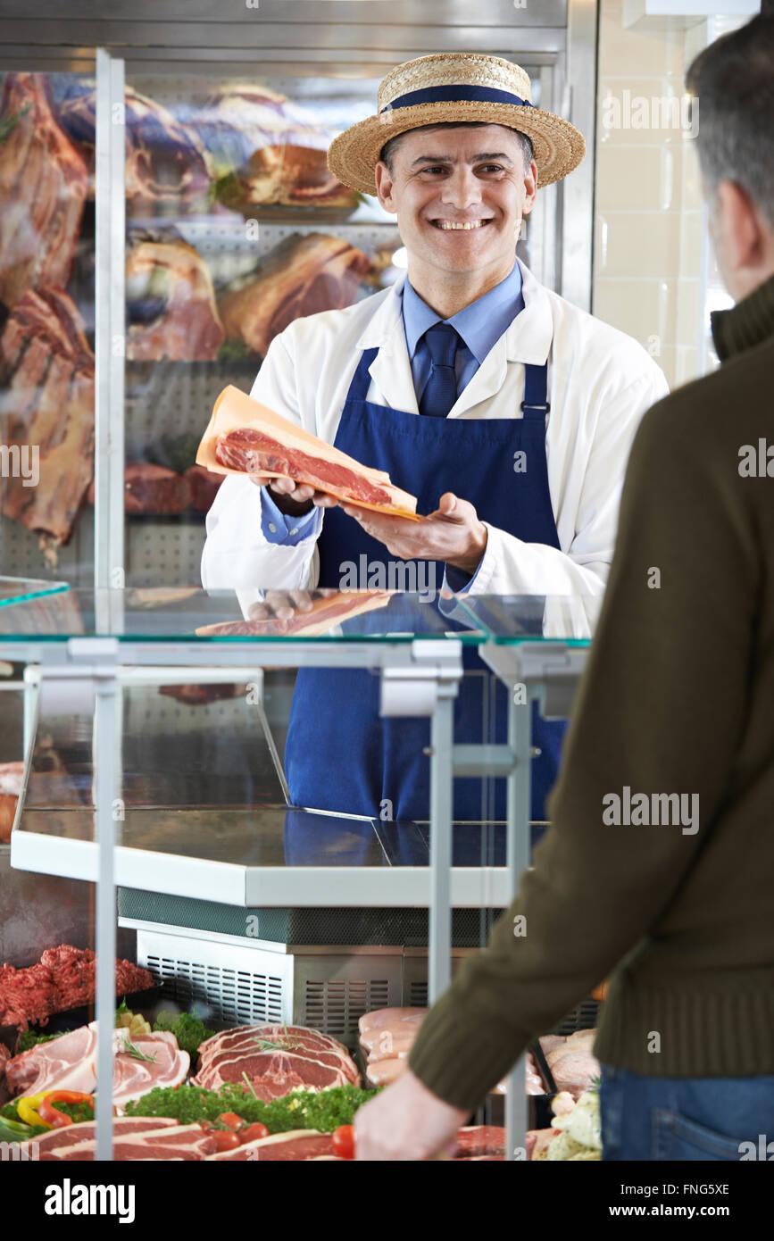 Butcher Serving Customer In Shop - Stock Image
