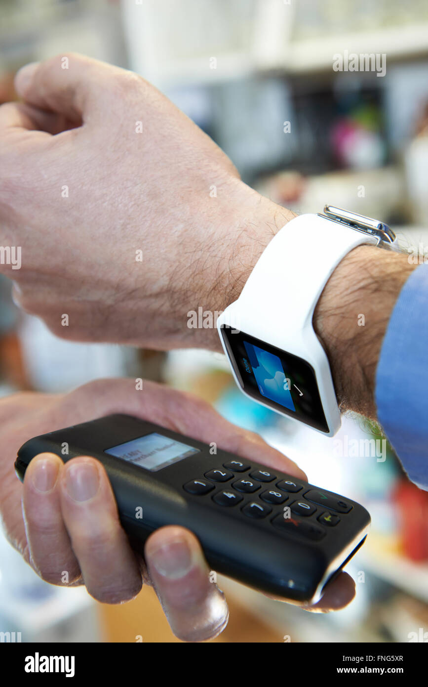 Man Using Contactless Payment App On Smart Watch In Store Stock Photo