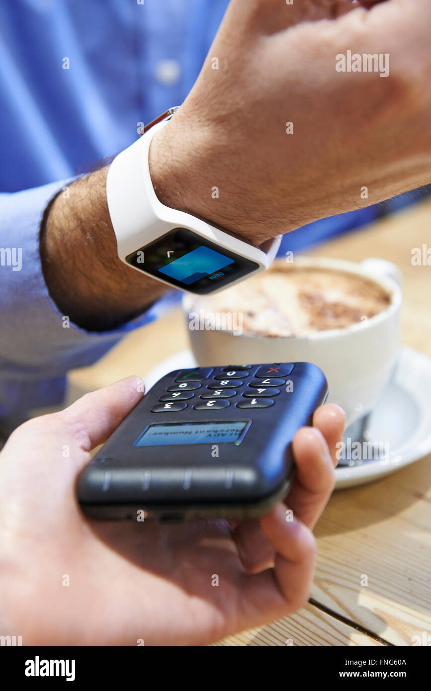Man Paying In Coffee Shop Using Contactless Payment App On Smart Watch - Stock Image