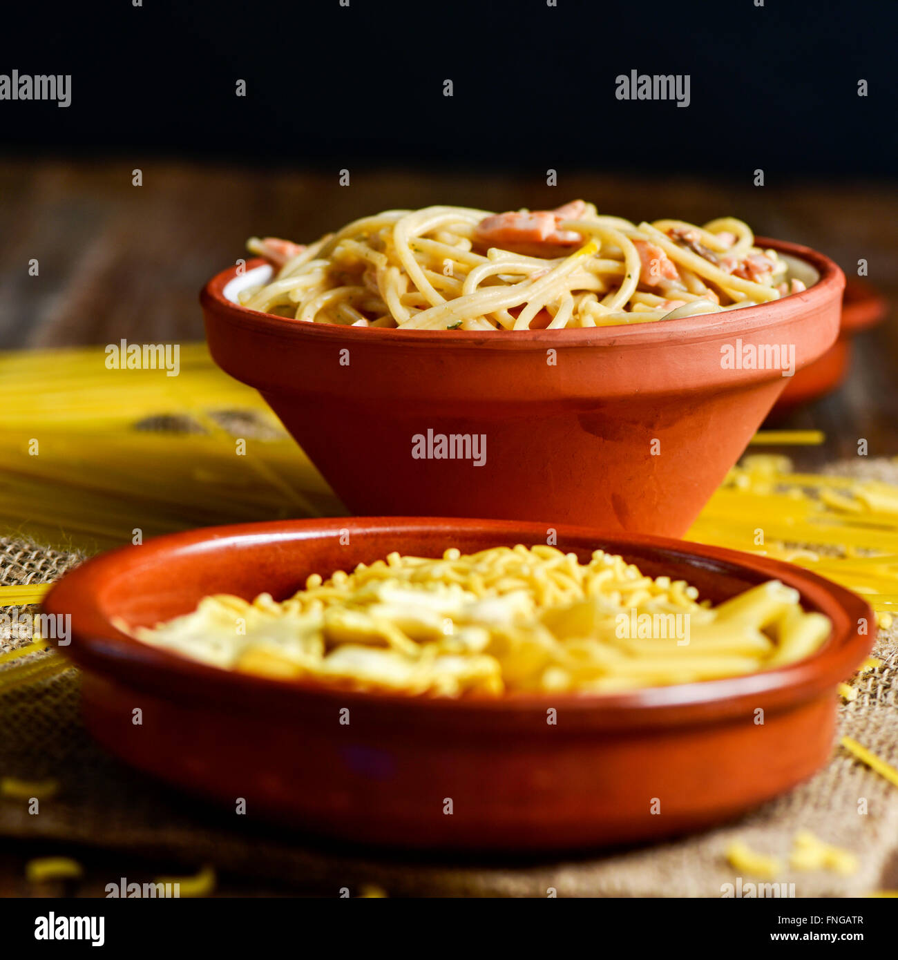 closeup of an earthenware plate with some uncooked pasta and an earthenware bowl with spaghetti alla carbonara, - Stock Image