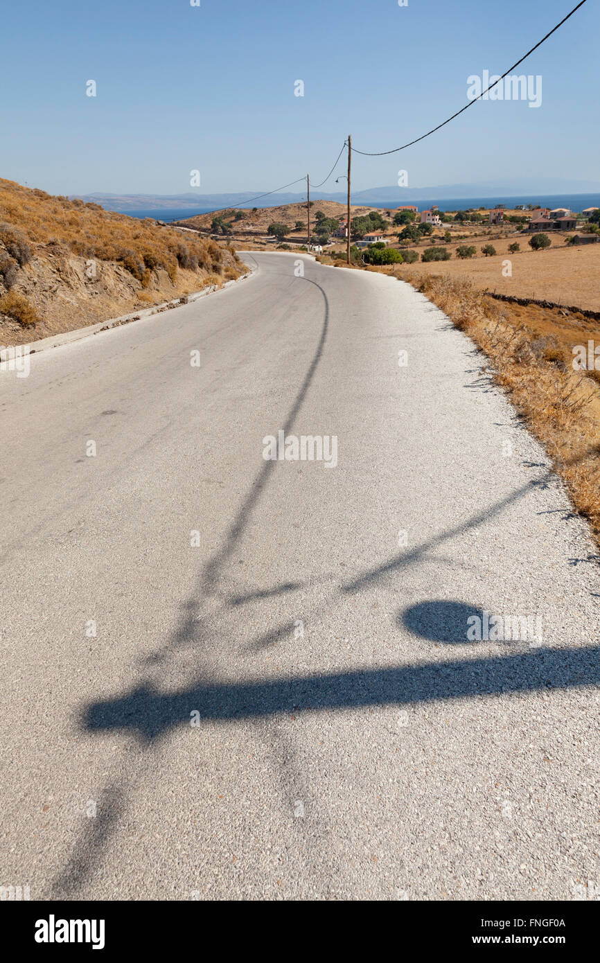 Lonely road with shadows in the heat of the day - Stock Image