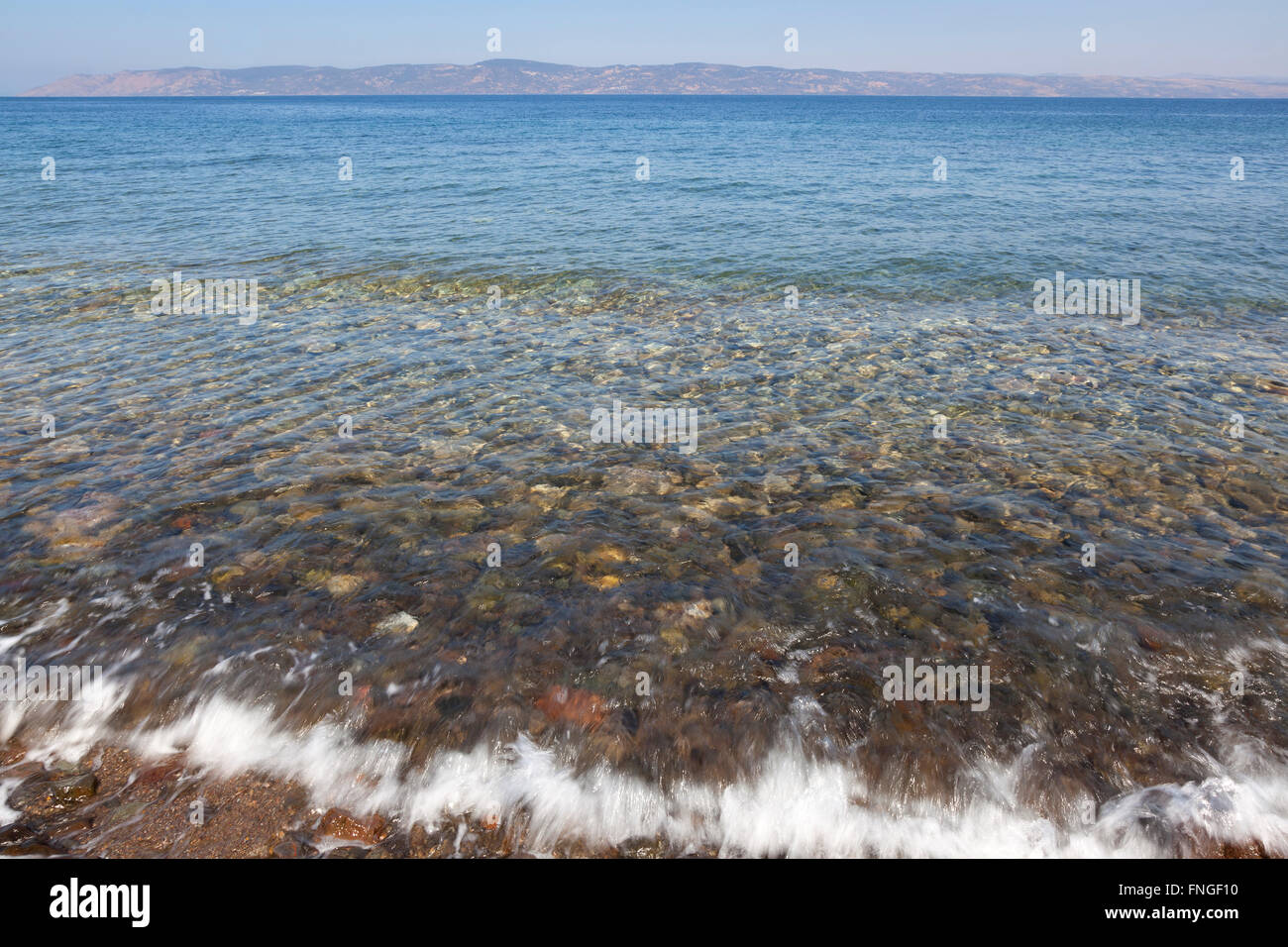 Clear sea water waves washing over pebbles in the Aegean Sea - Stock Image