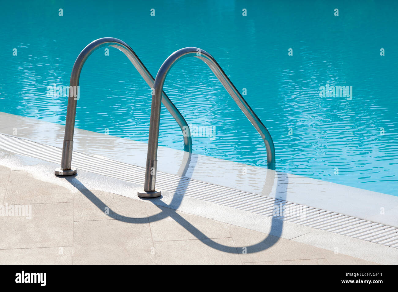 Metal stairs leading into a swimmingpool - Stock Image
