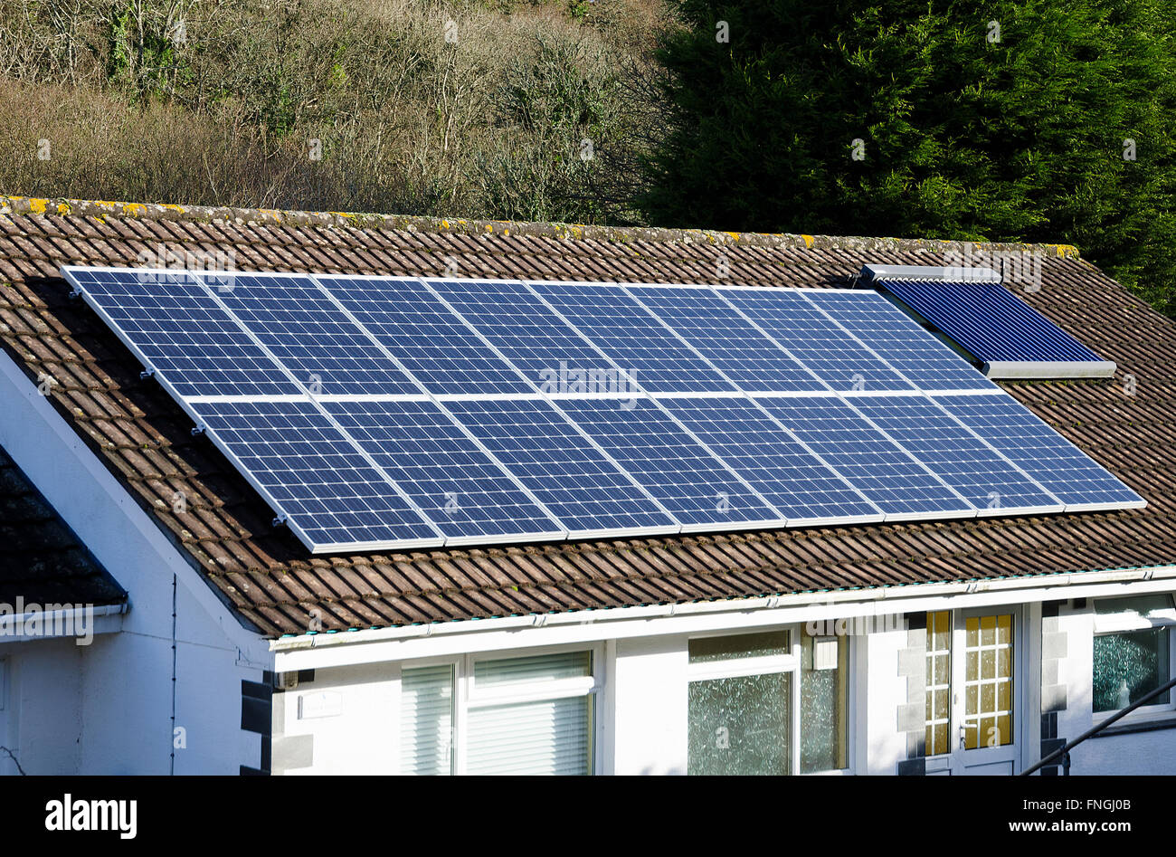 Solar panels on the roof of a bungalow in Cornwall, England, UK - Stock Image