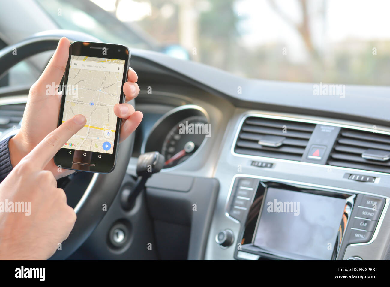 Smartphone hold by man with navigation map inside a car - Stock Image