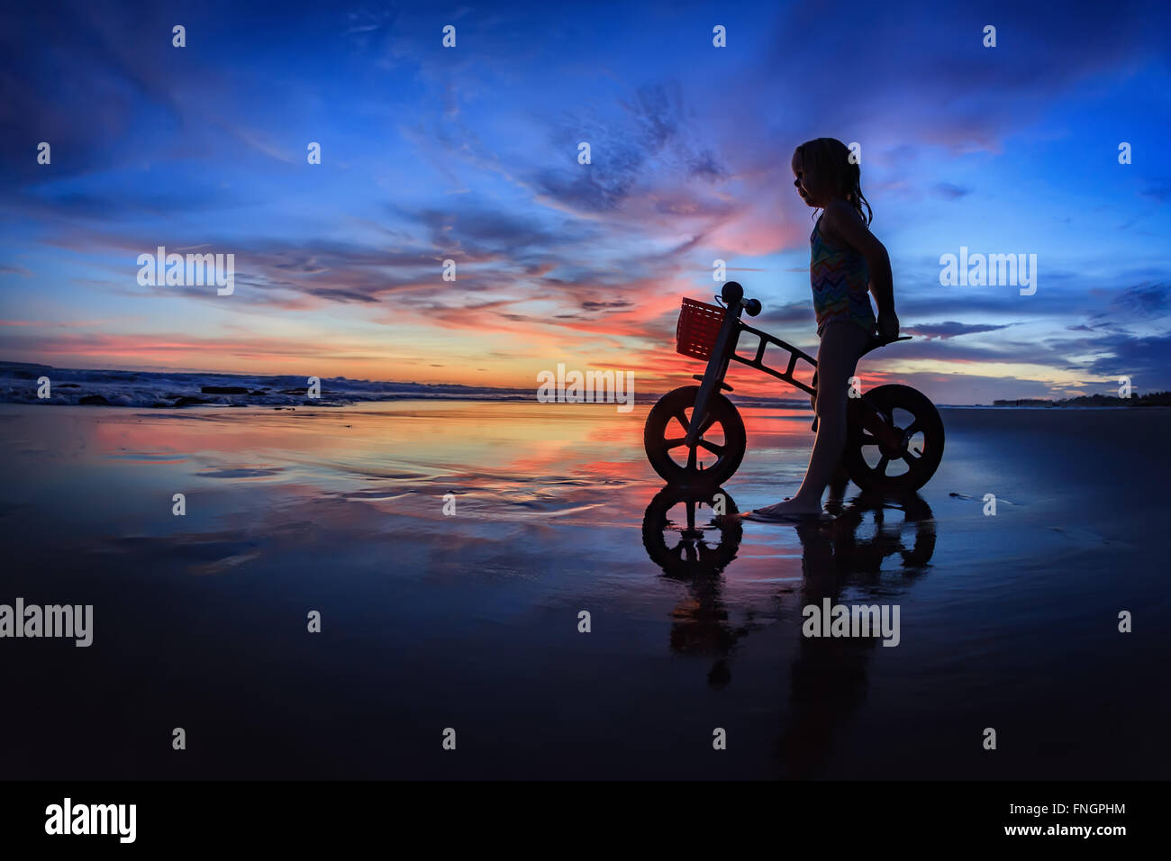 Black silhouette of little child - run bike rider stand on wet sand beach, look at sea surf and colourful sunset - Stock Image