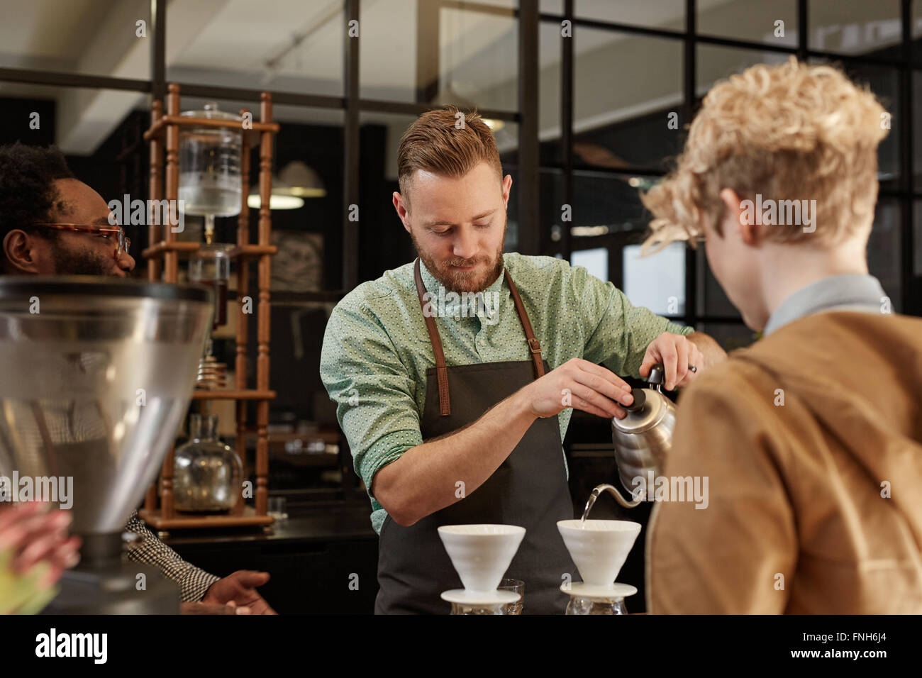 Barista pouring fresh coffee through filter in modern cafe - Stock Image