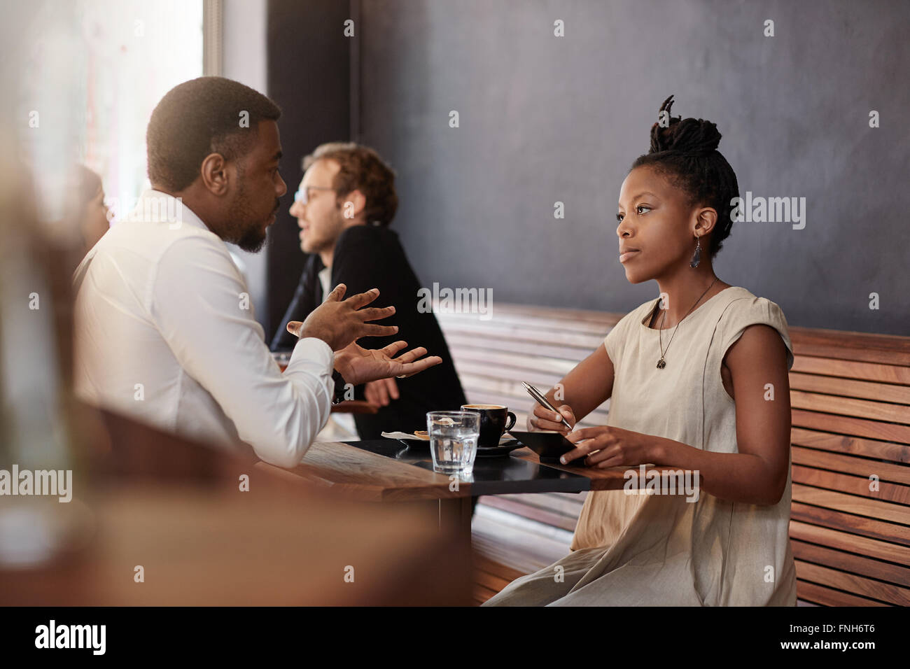 African woman having meeting with a man in busy cafe - Stock Image