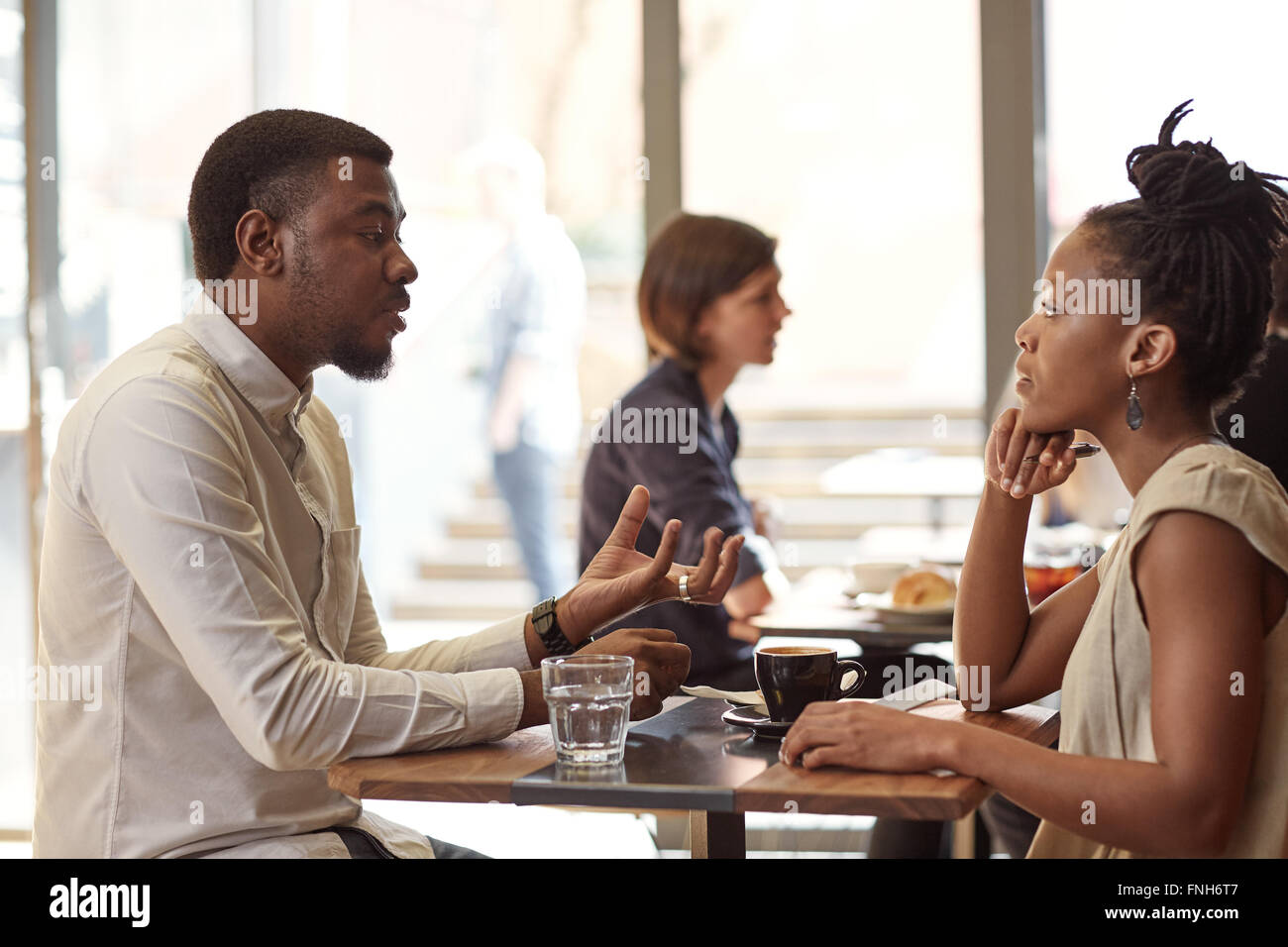 African entrepreneur explaining his idea to a businesswoman in c - Stock Image