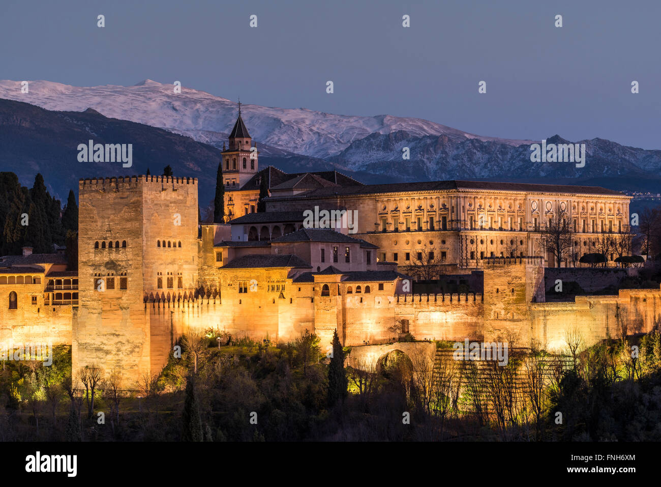 View at dusk of Alhambra palace with the snowy Sierra Nevada in the background, Granada, Andalusia, Spain - Stock Image