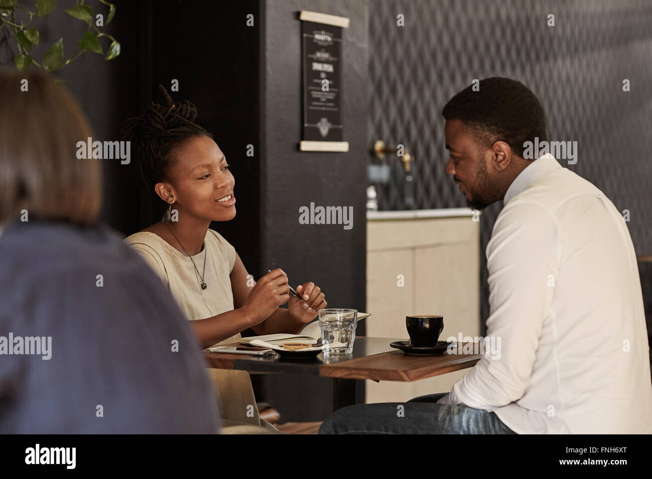 African couple enjoying coffee date in a modern cafe - Stock Image