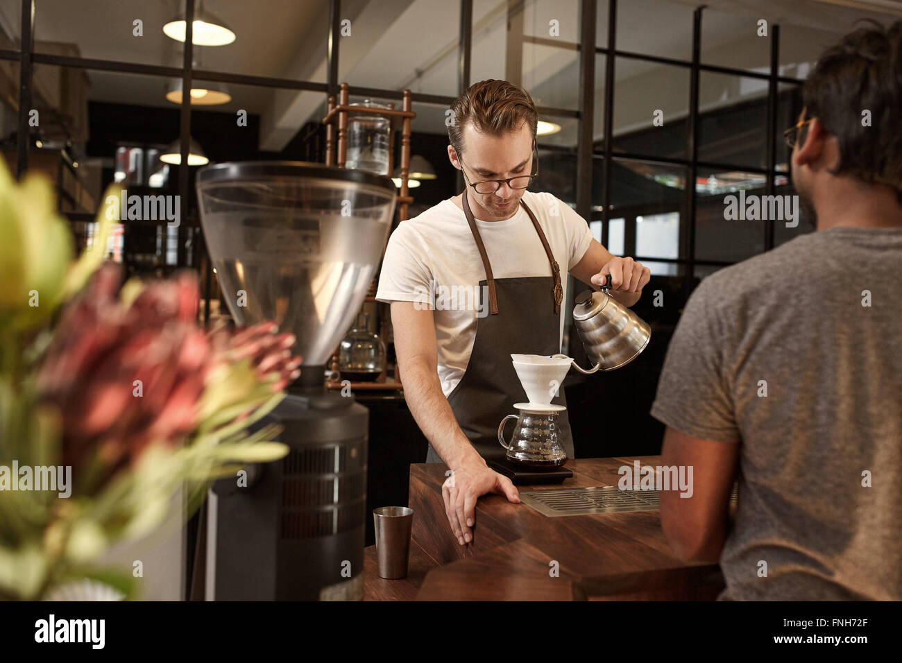 Barista pouring coffee through filter in modern cafe - Stock Image