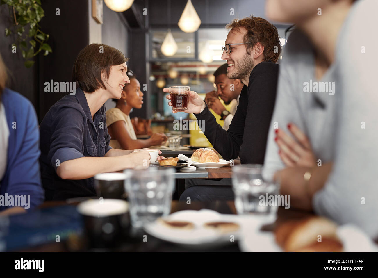 Busy cafe with a young couple smiling at each other - Stock Image